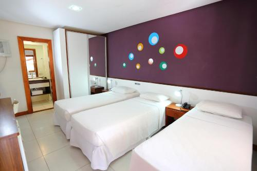 A bed or beds in a room at Flamingo Beach - Rede Soberano