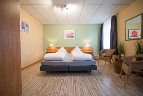 A bed or beds in a room at Rheinauer Hof - Das Hotel am Riedweg