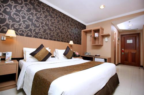 A bed or beds in a room at Galeri Ciumbuleuit Hotel