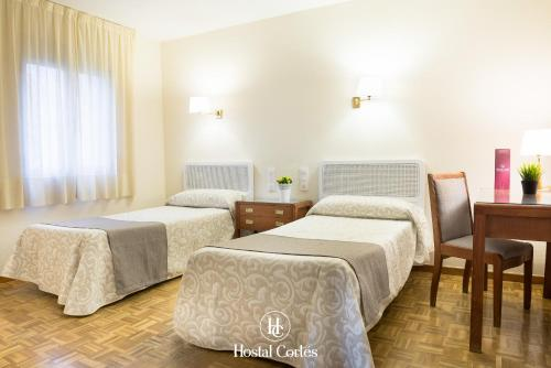 A bed or beds in a room at Hostal Cortes