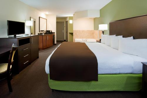 A bed or beds in a room at AmericInn by Wyndham Sibley