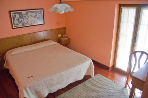 A bed or beds in a room at Pension Getariano