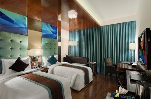 A bed or beds in a room at The Elanza Hotel, Bangalore