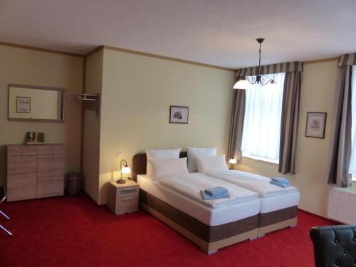 A bed or beds in a room at Hotel Friedchen mit eigener Fleischerei