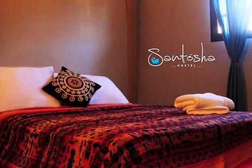 A bed or beds in a room at Santosha Hostel