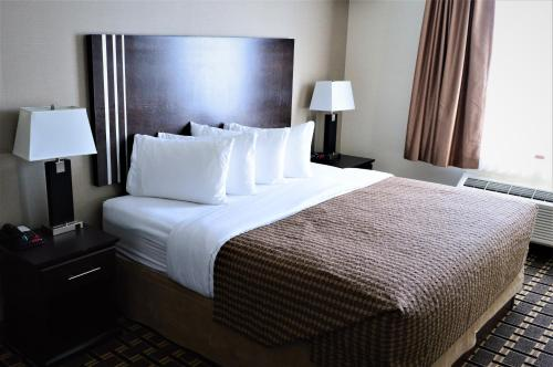 A bed or beds in a room at Sigma Inn & Suites