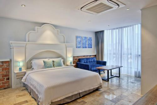 A bed or beds in a room at Timez Hotel Melaka