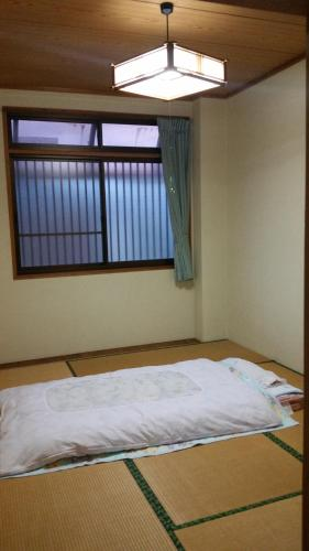 A bed or beds in a room at Minshuku Toshi