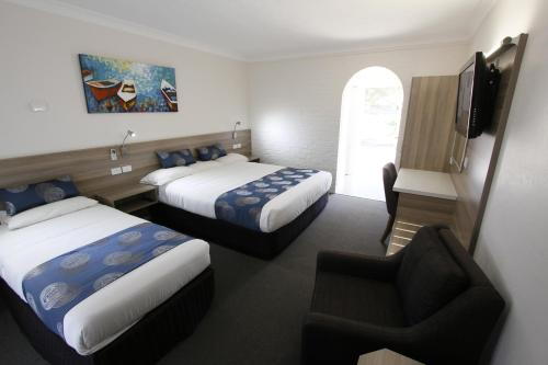 A bed or beds in a room at Aston Motel Yamba