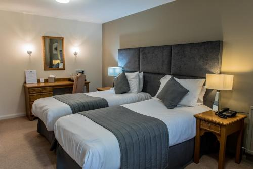 A bed or beds in a room at The Crown of Crucis Country Inn and Hotel