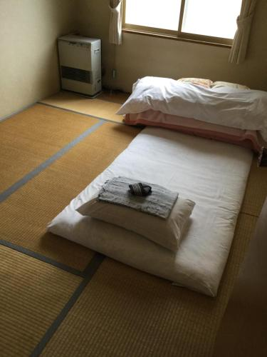 A bed or beds in a room at Business Hotel Matsuoka