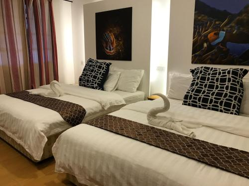 A bed or beds in a room at The Barat Perhentian