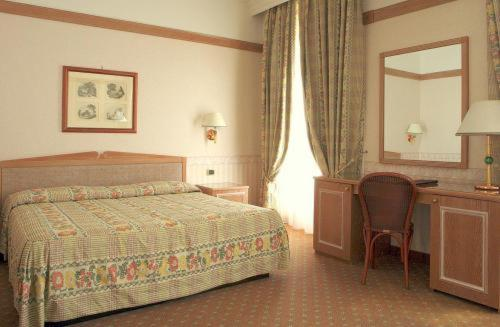 A bed or beds in a room at Grand Hotel Delle Terme Re Ferdinando