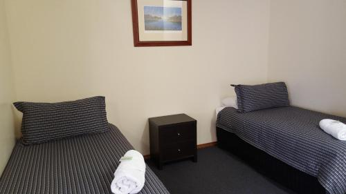 A bed or beds in a room at Gateway Motor Inn