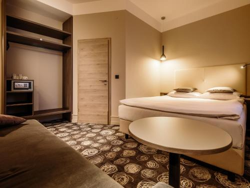 A bed or beds in a room at Hotel Center Novo Mesto