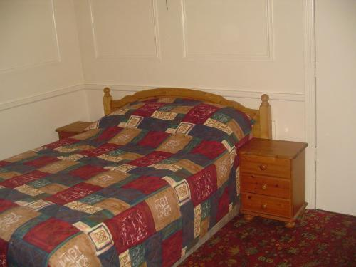 A bed or beds in a room at Fawlty Towers