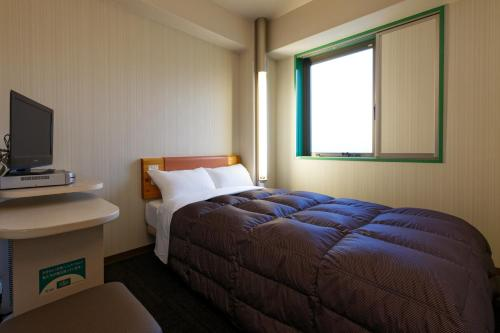 A bed or beds in a room at R&B Hotel Kumamoto Shimotori