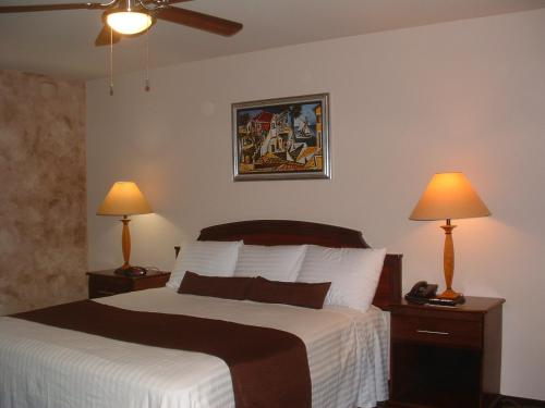 A bed or beds in a room at The Sunset Inn