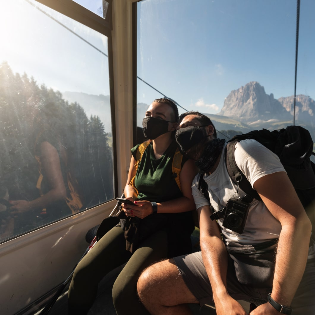 Couple wearing masks riding a gondola through a mountain range
