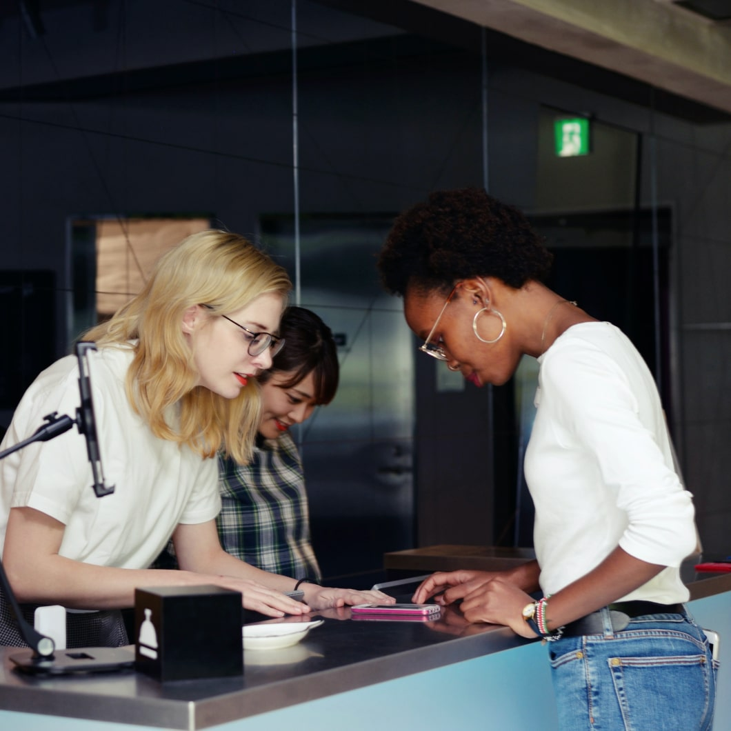 Two women at a front desk helping a new guest check in