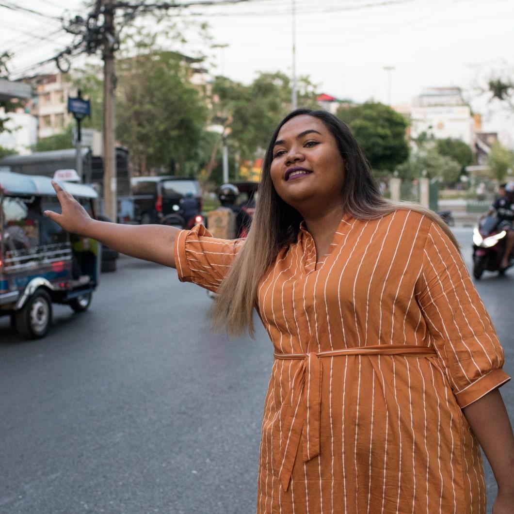 Una viaggiatrice che chiama un taxi in una destinazione soleggiata