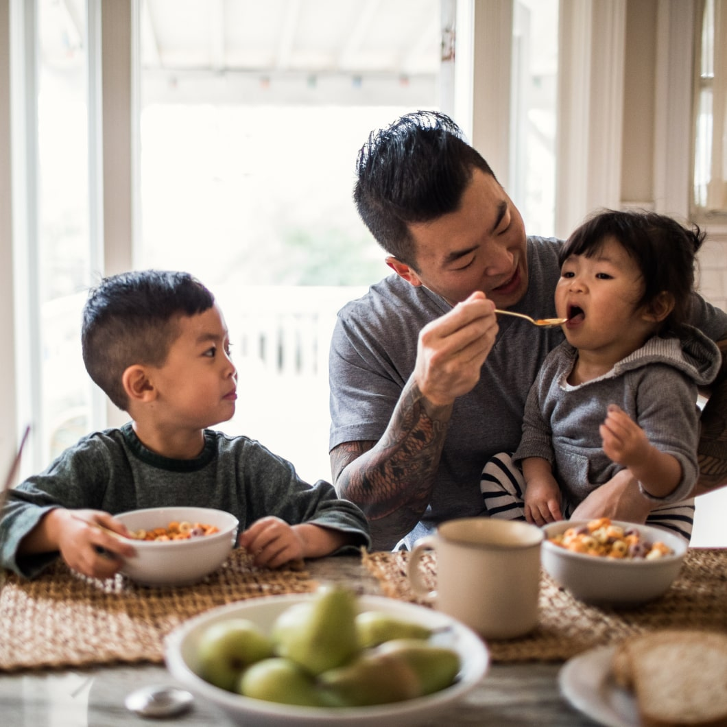 Father having breakfast with his two young kids