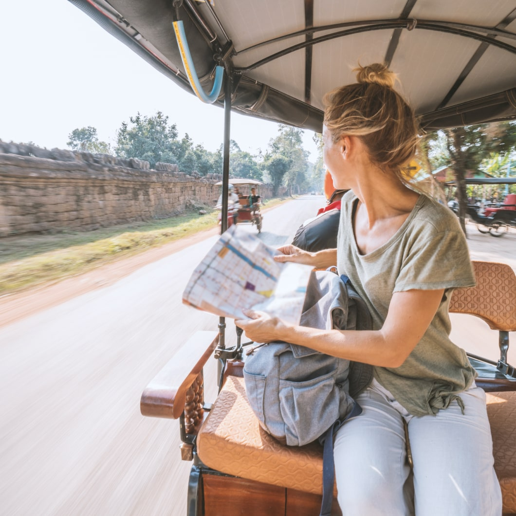 A traveller with a map riding on the back of a rickshaw
