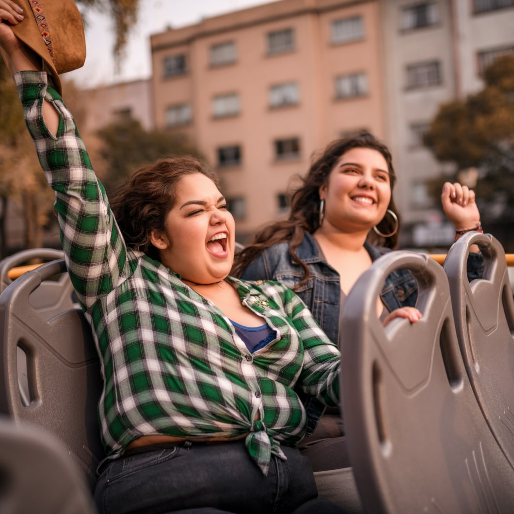 Two happy travellers riding on the top of a double-decker bus