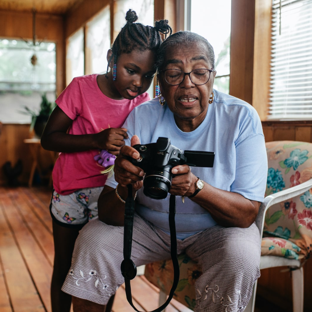 A young girl and her grandmother looking at photos on a digital camera