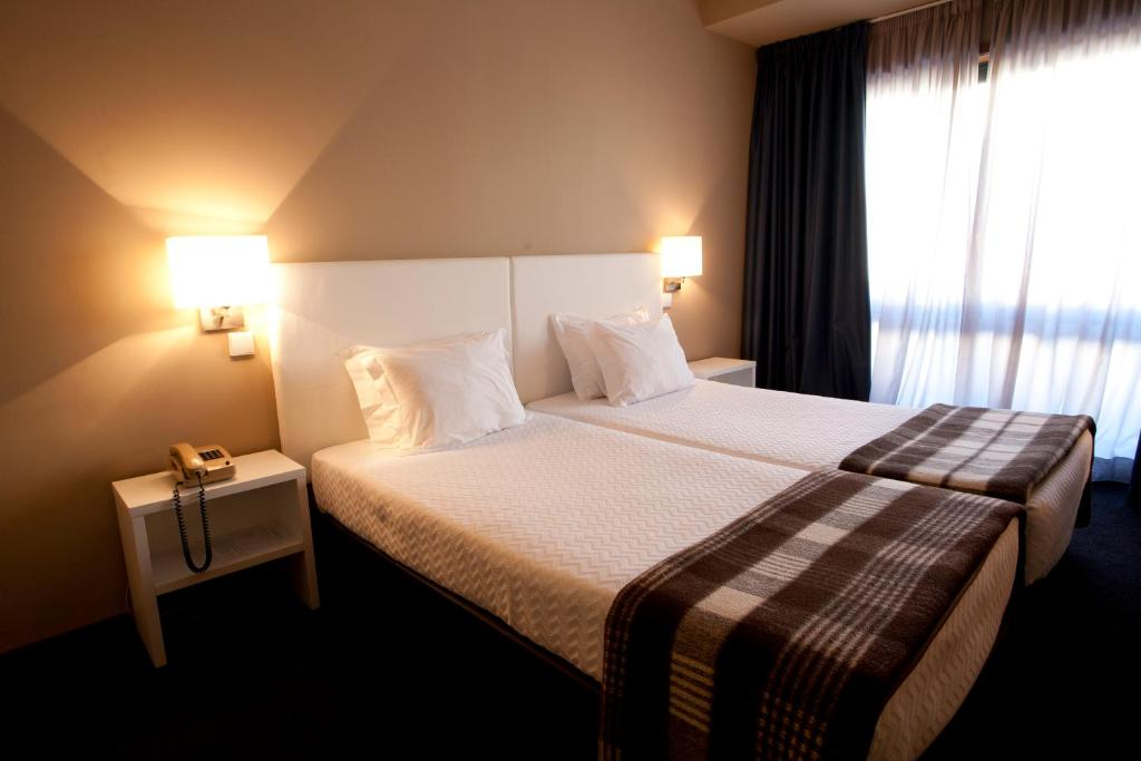 A bed or beds in a room at Porto Antas Hotel