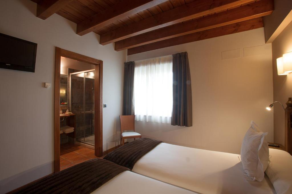 A bed or beds in a room at Hotel-Apartamento Rural Atxurra
