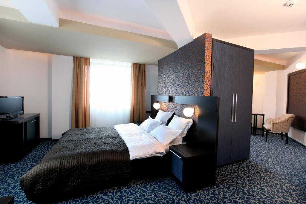 Un pat sau paturi într-o cameră la Ambiance Hotel
