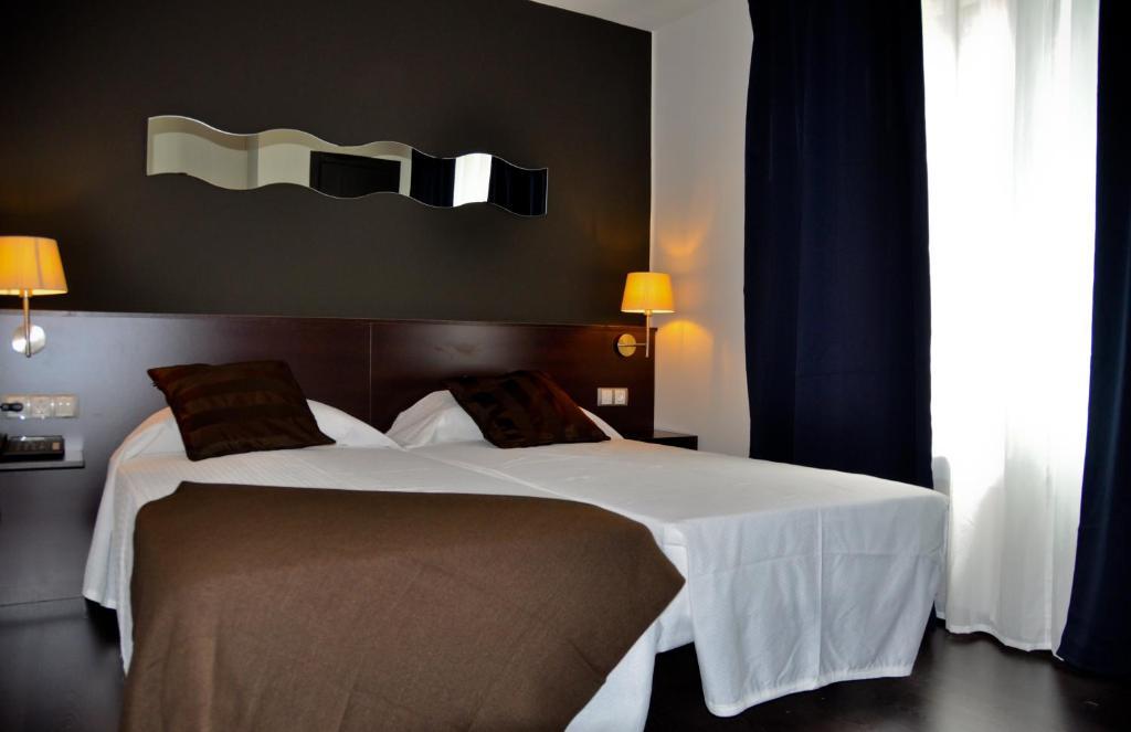 A bed or beds in a room at Hostal La Rotonda