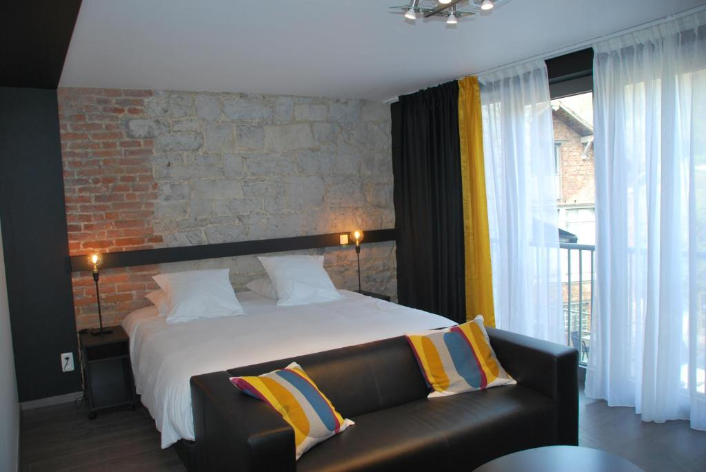 A bed or beds in a room at Le Durbuysien
