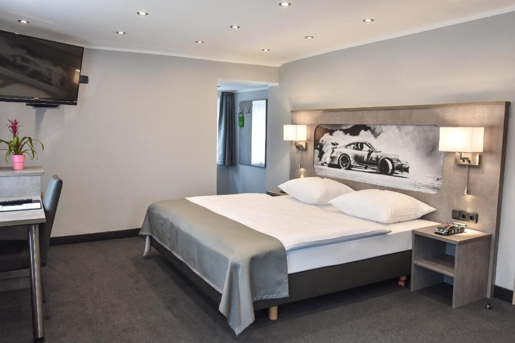A bed or beds in a room at GT3 das sportliche Hotel