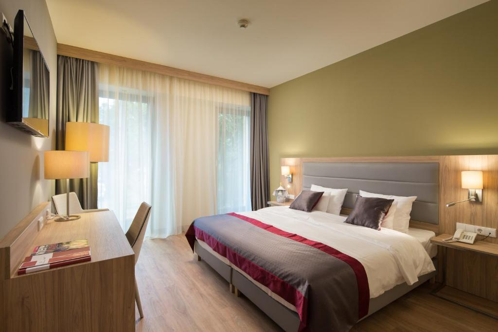 A bed or beds in a room at Verdi Grand Hotel