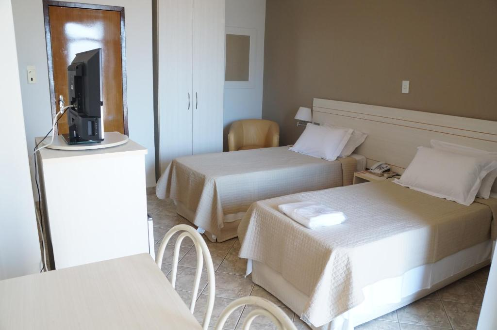 A bed or beds in a room at Manhuaçu Center Hotel