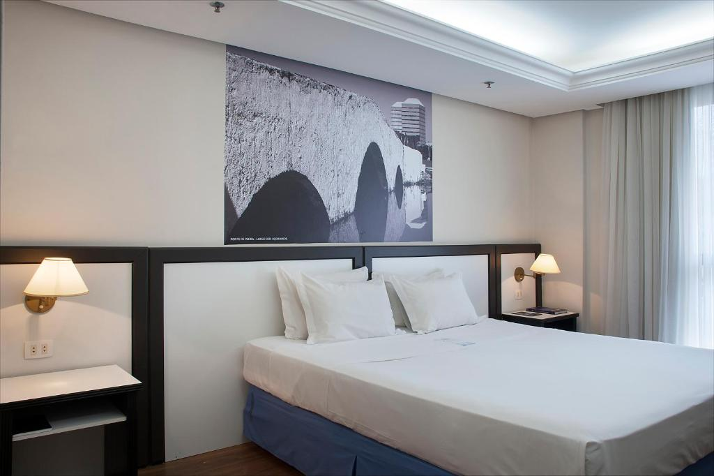 A bed or beds in a room at Master Grande Hotel - Centro Histórico