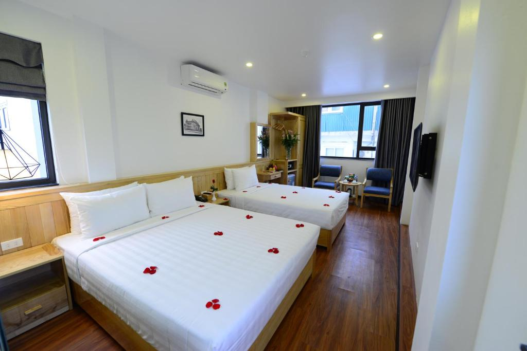 A bed or beds in a room at Blue Hanoi Inn Luxury Hotel & Spa