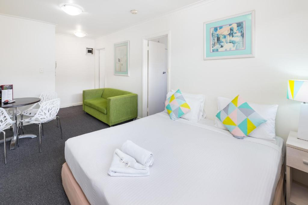 A bed or beds in a room at City Edge East Melbourne Apartment Hotel