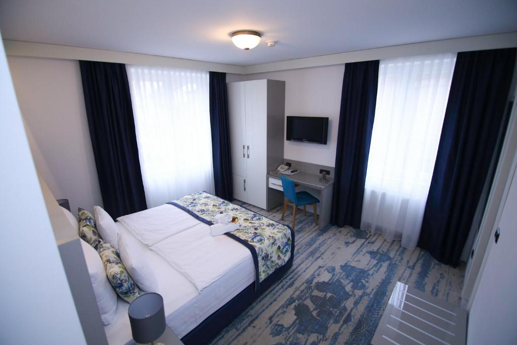 A bed or beds in a room at Old Town Hotel