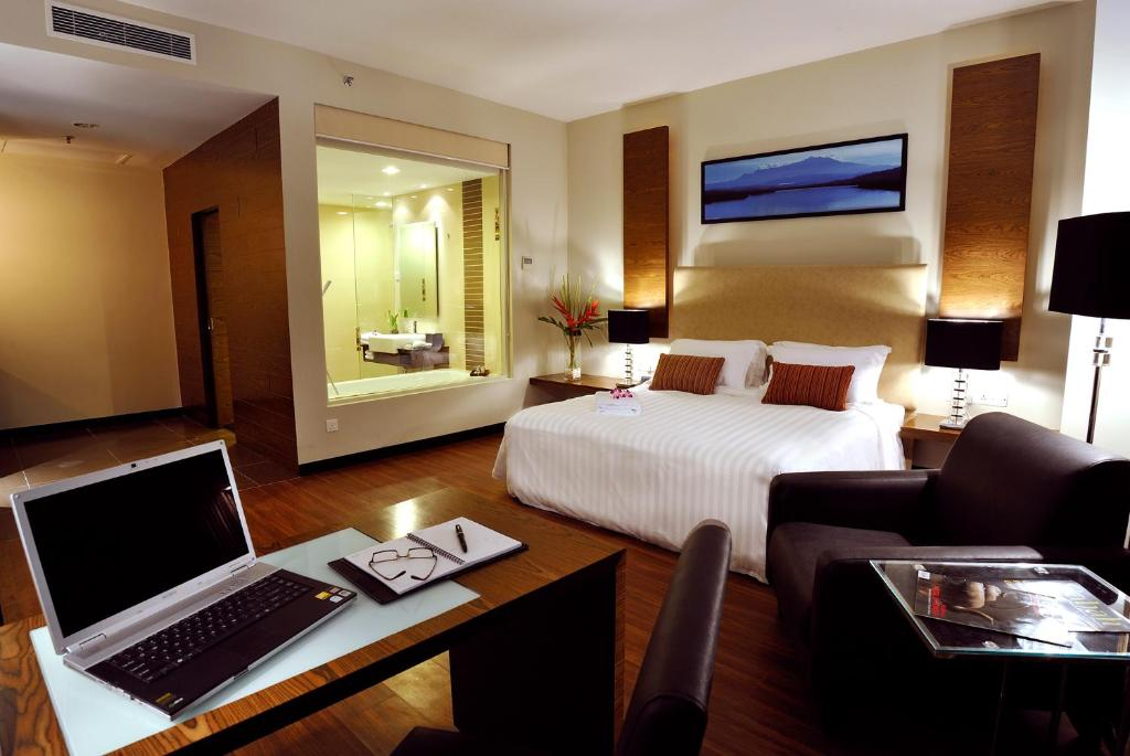 A bed or beds in a room at Grand Borneo Hotel