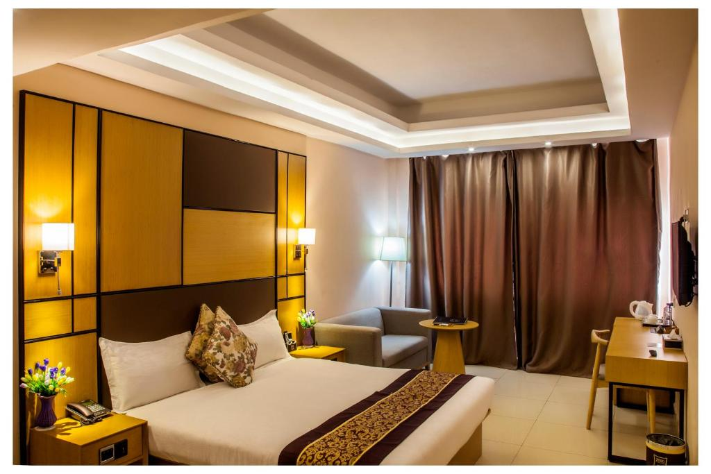 A bed or beds in a room at 2000 Hotel Downtown Kigali
