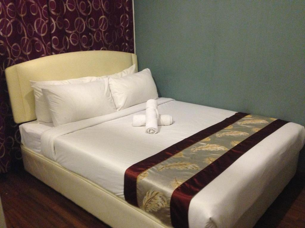 A bed or beds in a room at Woodpecker Lodge, Kuching