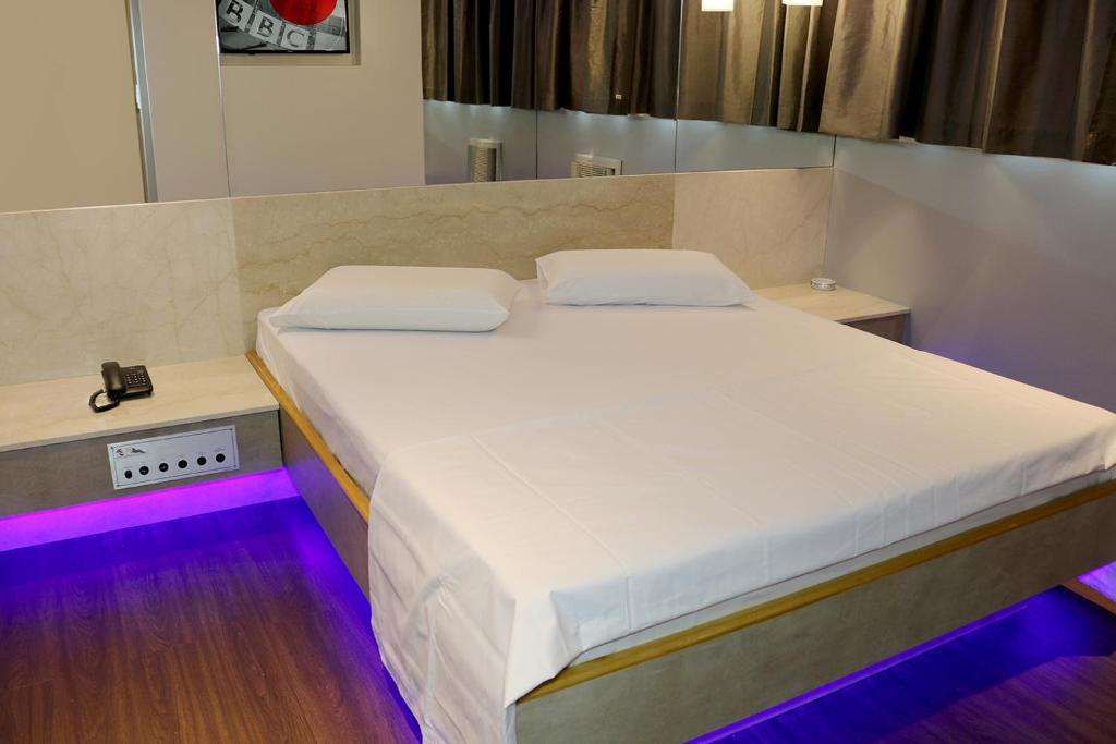 A bed or beds in a room at Hotel Praia Grande Niterói