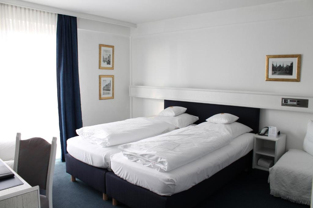 A bed or beds in a room at Hotel Windthorst