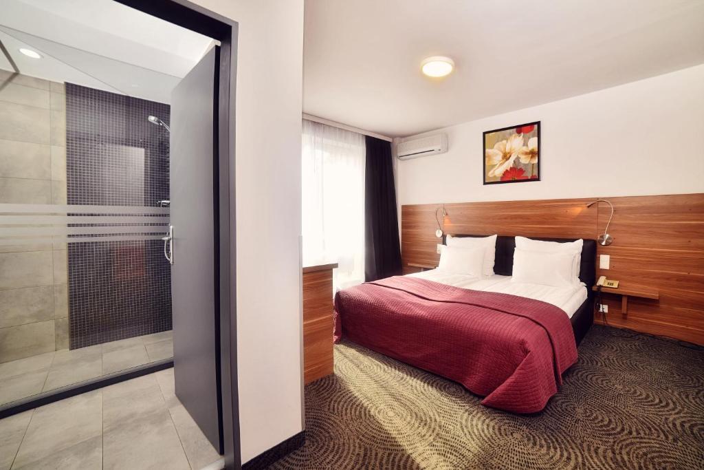 Un pat sau paturi într-o cameră la Hotel President