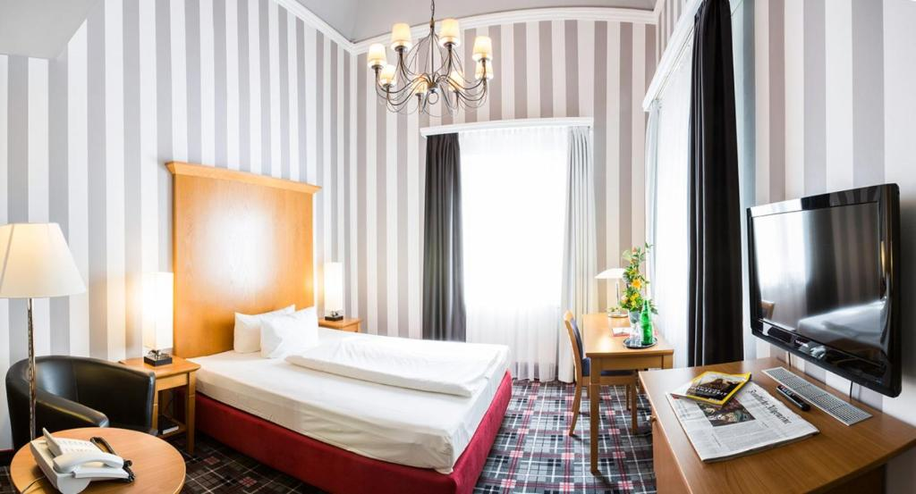 A bed or beds in a room at Dittmanns Grünau Hotel