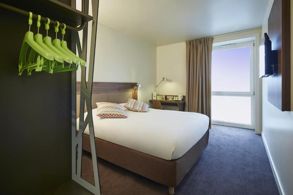 A bed or beds in a room at Campanile Paris Sud - Saclay