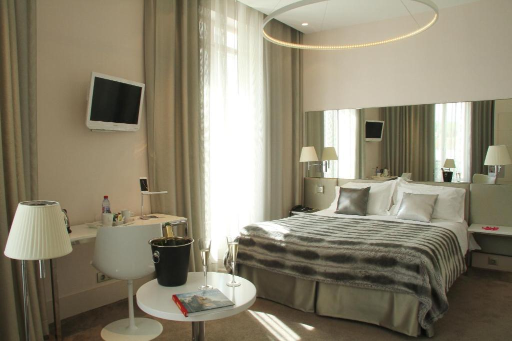 A bed or beds in a room at Le César Hôtel